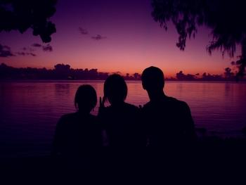 人物のシルエットと夕日