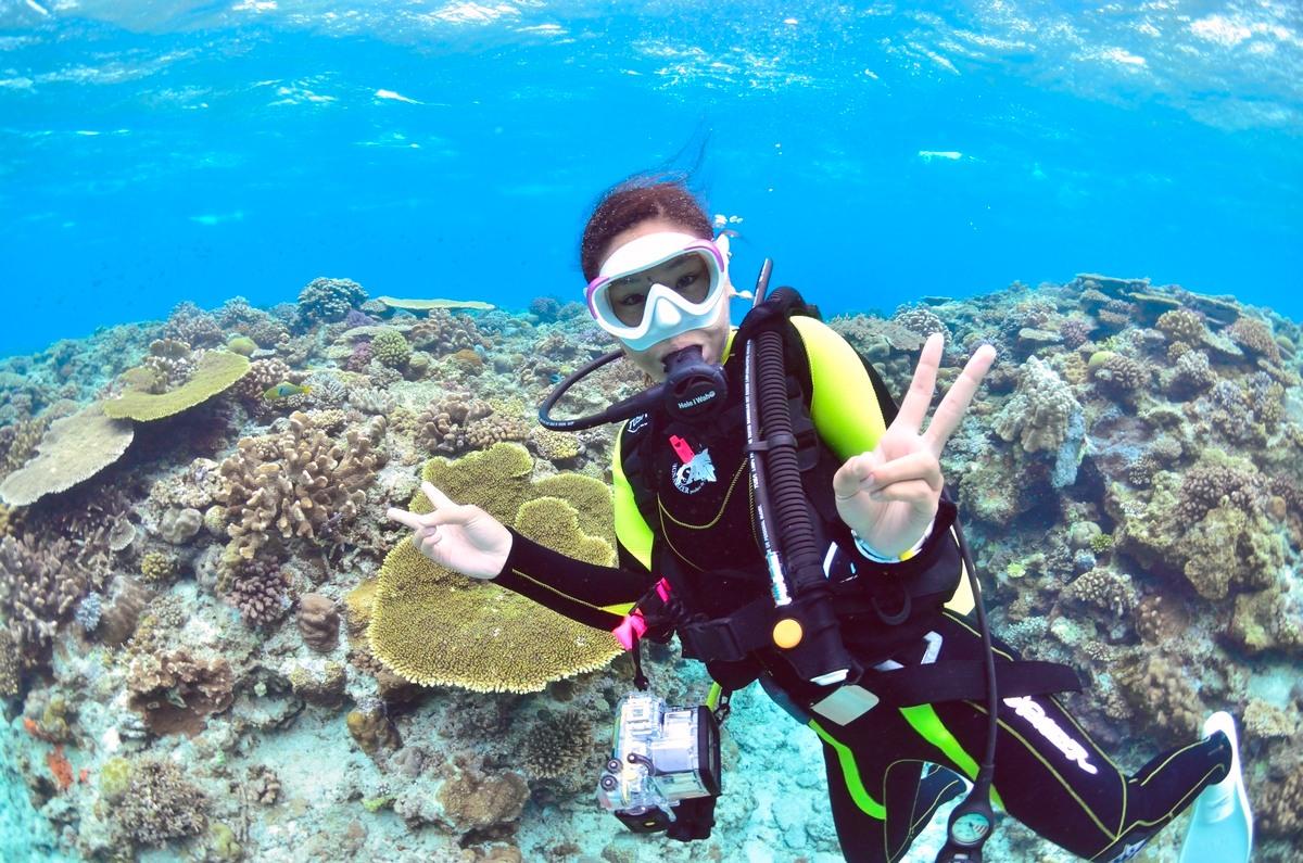 女性ダイバーと珊瑚礁の群生